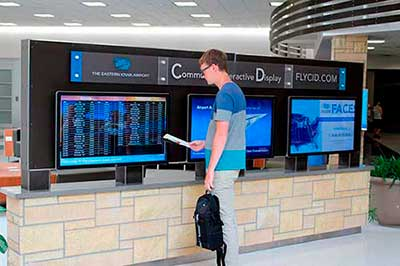 Airport Digital Signage Showing Three Screens With Flight Status, Advertising Videos and Live Digital Feeds